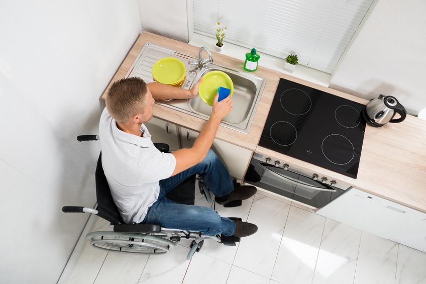 Homme en fauteuil qui fait la vaisselle